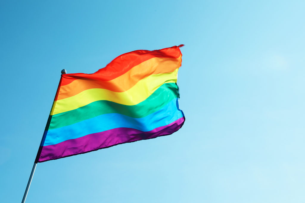 Pride flag against a blue backdrop